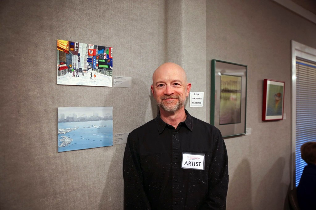 David Prescott poses beside his work featured in the 2017 Student & Faculty exhibition.